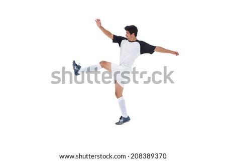 Football player in white kicking on white background - stock photo