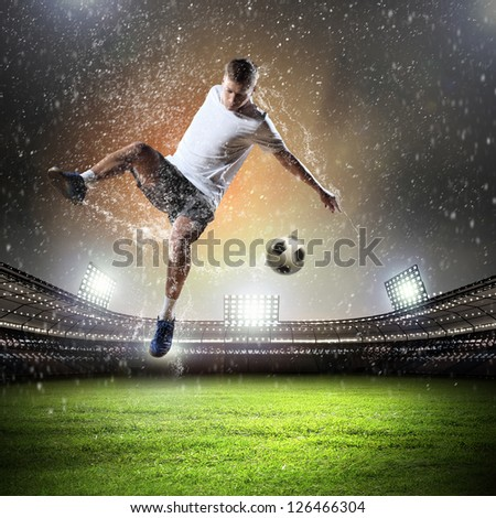 football player in white shirt striking the at the stadium under the rain