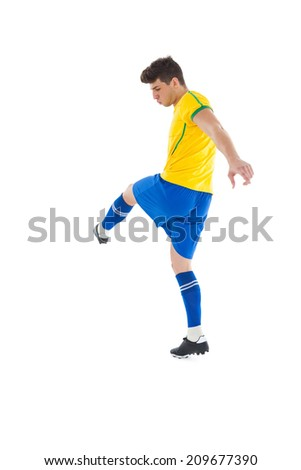 Football player in yellow kicking on white background - stock photo