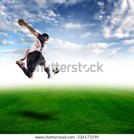 football player jumping kick ball on the field of blue sky