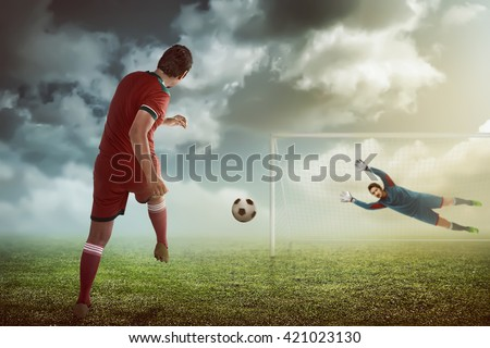 Football player kick ball and goalkeeper try to catch - stock photo