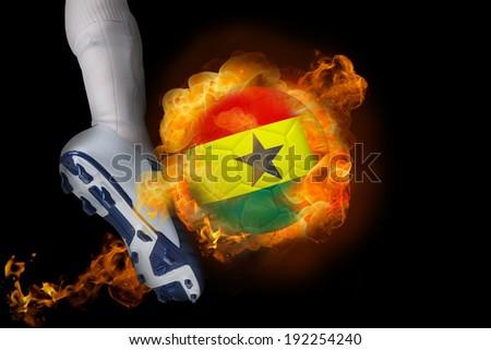 Football player kicking flaming ghana flag ball against black - stock photo