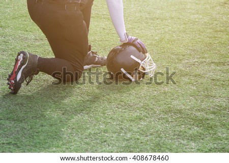 Football player kneeling on the field and holding the helmet