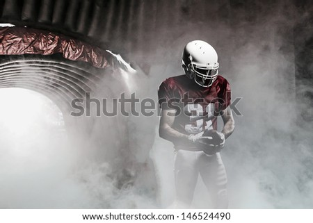 Football player, leaving a smoky tunnel, ready to get on the field - stock photo