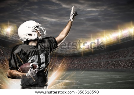 Football Player on a black uniform celebrating on a Stadium.