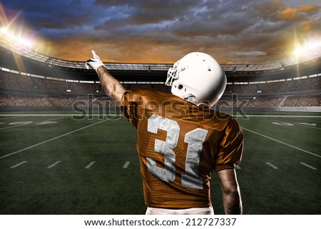 Football Player on a Orange uniform celebrating on a stadium background.