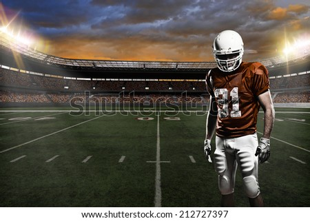 Football Player on a Orange uniform, on a stadium background.