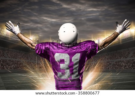 Football Player on a pink uniform celebrating on a Stadium.