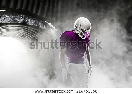 Football player, on a pink uniform, leaving a smoky tunnel, ready to get on the field.