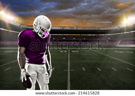 Football Player on a pink uniform, on a stadium background.