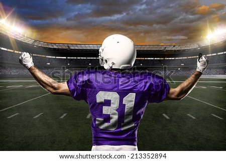 Football Player on a purple uniform celebrating on a stadium background.