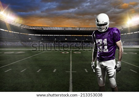 Football Player on a purple uniform, on a stadium background.