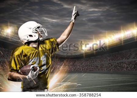 Football Player on a yellow uniform celebrating on a Stadium.