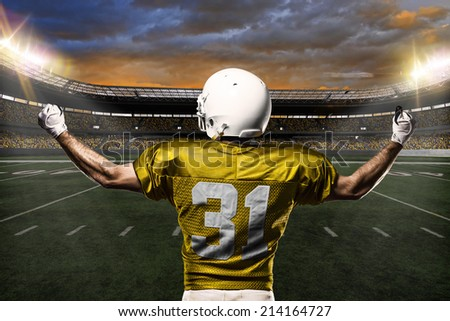 Football Player on a yellow uniform celebrating on a stadium background.