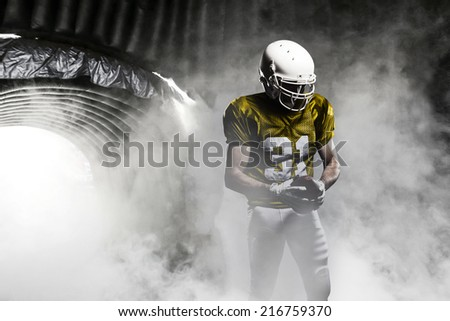 Football player, on a yellow uniform, leaving a smoky tunnel, ready to get on the field.