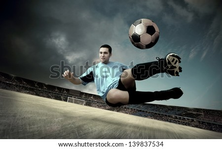 football player on soccer field of stadium with drammatic sky - stock photo