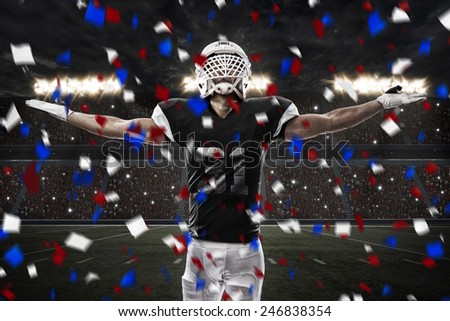 Football Player with a Black uniform celebrating, on a stadium. - stock photo
