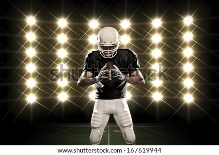 Football Player with a black uniform in front of lights - stock photo