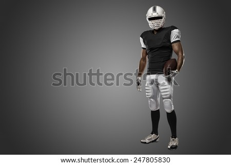 Football Player with a black uniform on a black background. - stock photo