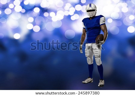 Football Player with a blue uniform on a blue lights background. - stock photo