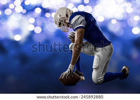 Football Player with a blue uniform on his knees, on a blue lights background.