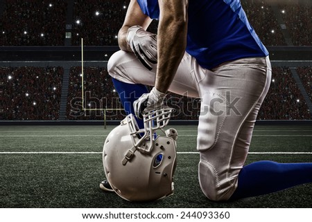 Football Player with a blue uniform on his knees, on a Stadium. - stock photo