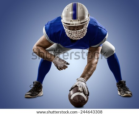 Football Player with a blue uniform on the scrimmage line, on a blue background. - stock photo