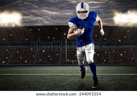 Football Player with a blue uniform running on a stadium. - stock photo