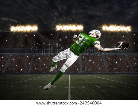 Football Player with a green uniform catching a ball on a stadium. - stock photo