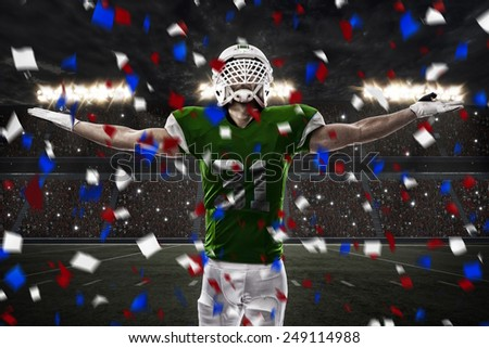 Football Player with a green uniform celebrating, on a stadium. - stock photo
