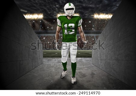 Football Player with a green uniform entering a stadium tunnel. - stock photo