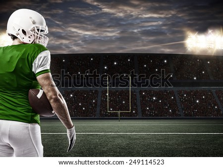 Football Player with a green uniform on a stadium.