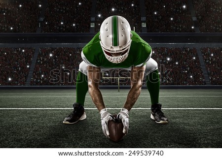 Football Player with a green uniform on the scrimmage line, on a stadium. - stock photo