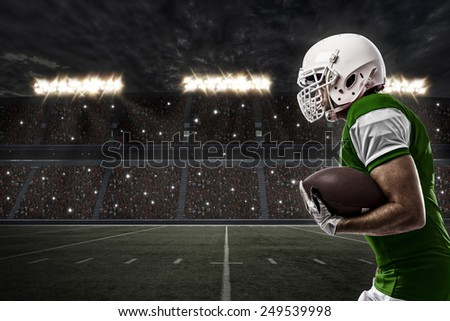 Football Player with a green uniform running on a stadium. - stock photo