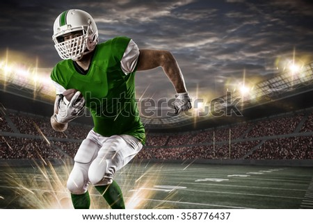 Football Player with a green uniform running on a stadium.