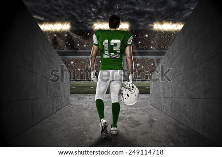 Football Player with a green uniform walking out of a Stadium tunnel. - stock photo