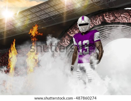 Football Player with a pink uniform coming out of a stadium tunnel.