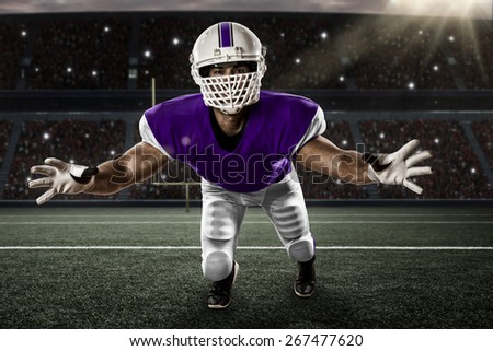 Football Player with a purple uniform making a tackle on a stadium. - stock photo