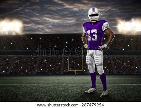 Football Player with a purple uniform on a stadium. - stock photo