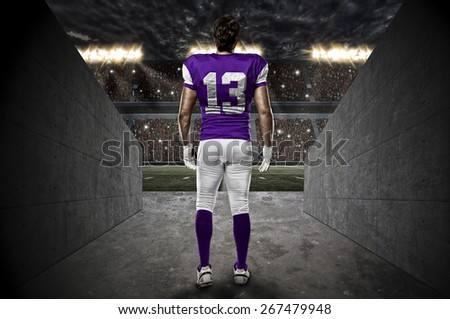Football Player with a purple uniform walking out of a Stadium tunnel. - stock photo