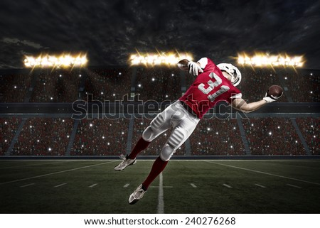 Football Player with a red uniform catching a ball on a stadium. - stock photo