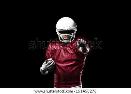 Football Player with a Red uniform celebrating on a Black background. - stock photo