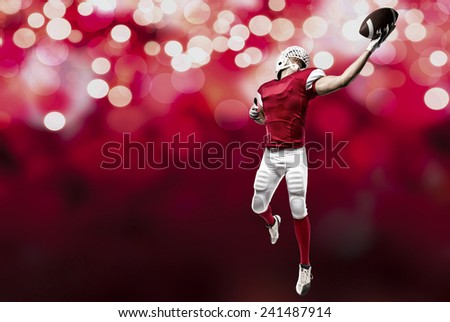 Football Player with a red uniform making a catch on a red lights background. - stock photo