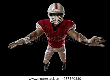 Football Player with a red uniform making a tackle on a Black background. - stock photo