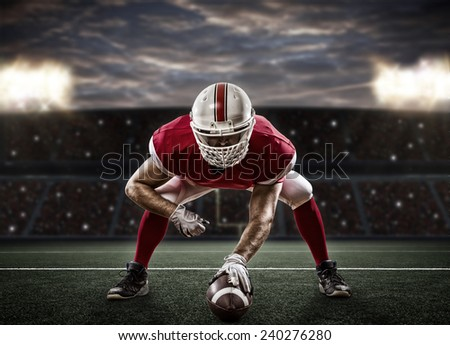 Football Player with a red uniform on the scrimmage line, on a stadium. - stock photo