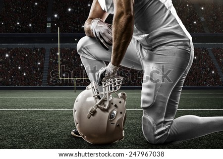 Football Player with a white uniform on his knees, on a Stadium. - stock photo