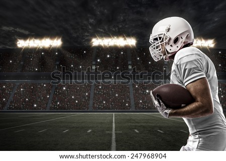 Football Player with a white uniform running on a stadium. - stock photo