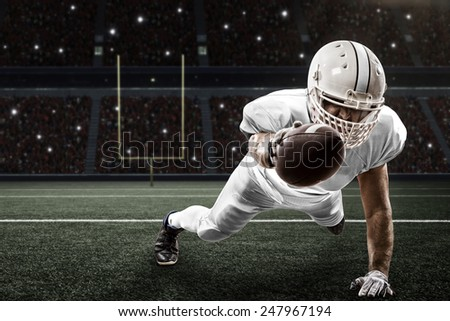 Football Player with a white uniform scoring on a Stadium. - stock photo