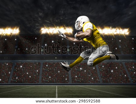 Football Player with a yellow uniform running on a stadium. - stock photo
