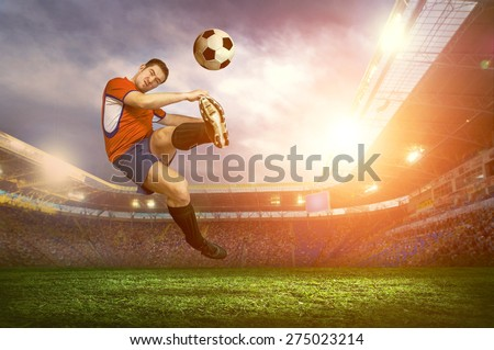 Football player with ball on field of stadium